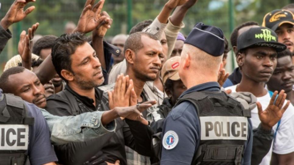 """Des migrants de la """"jungle"""" à Calais attendent un bus, encadré par la police, le 13 septembre"""