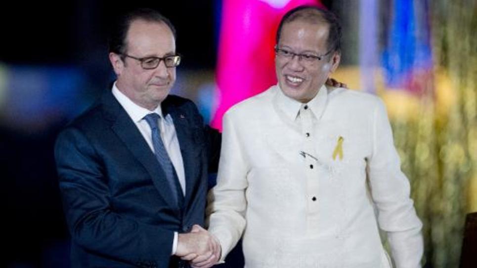 Les présidents français Francois Hollande (G) et philippin Benigno Aquino se serrent la main le 26 février 2015 à Manille