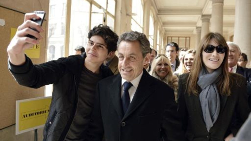 """Un jeune homme prend un """"selfie"""" avec Nicolas Sarkozy qui quitte son bureau de vote pour le premier tour des élections municipales, le 23 mars 2014 en compagnie de son épouse Carla Bruni Sarkozy"""