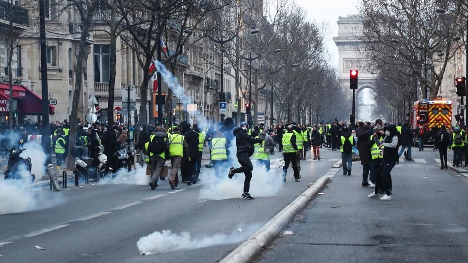 """Un manifestant renvoit une grenade lacrymogène lors de la 13e manifestation des """"gilets jaunes"""" à Paris le 9 février 2019"""