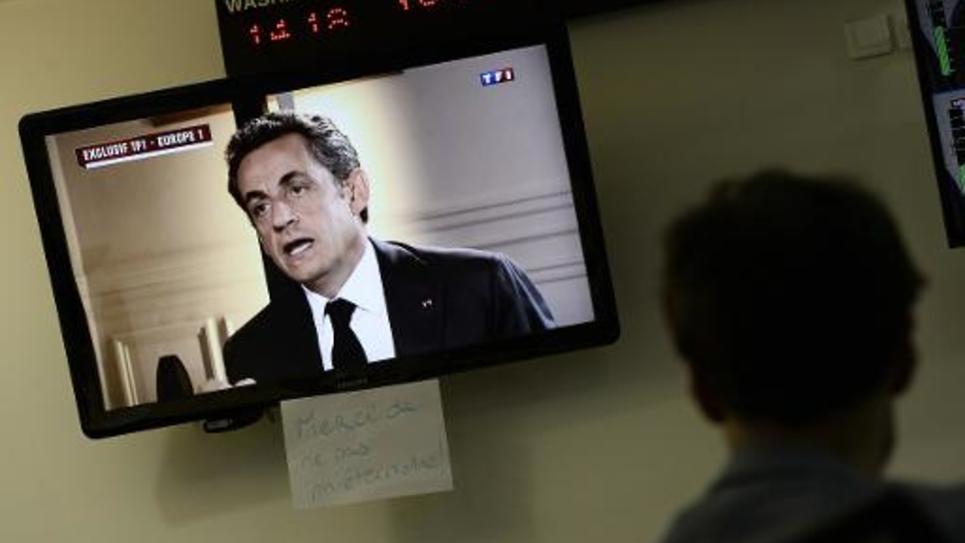 Un journaliste regarde Nicolas Sarkozy lors de son intervention télévisée pré-enregistrée, le 2 juillet 2014 à Paris
