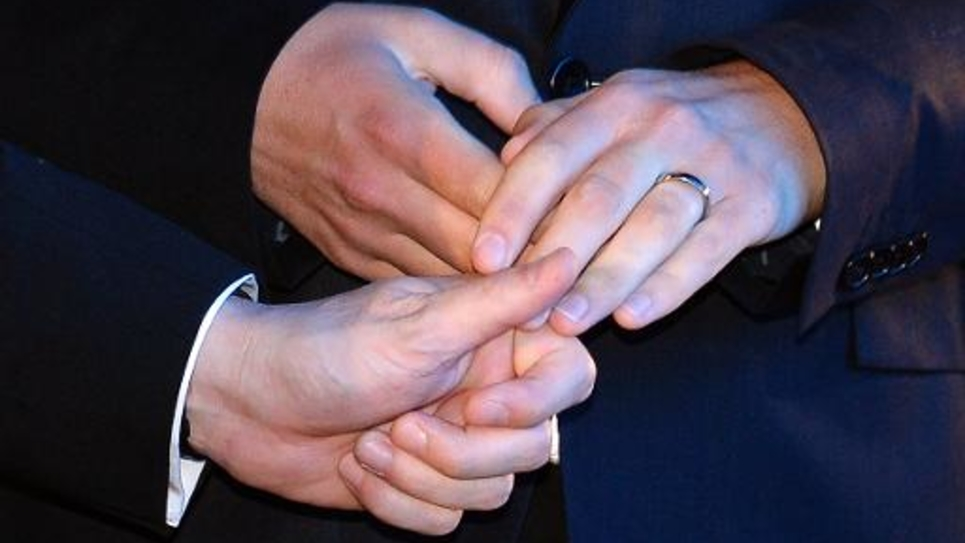 Deux hommes s'échangent les alliances lors de leur mariage, en mai 2013