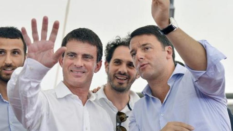 Le Premier ministre italien Matteo Renzi (droite) et son homologue français Manuel Valls saluent à leur arrivée à Festa dell'Unita à Bologne le 7 septembre 2014