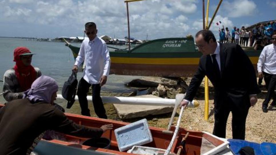 François Hollande parle avec des pêcheurs sur l'île des Philippines de Guiuan le 27 février 2015