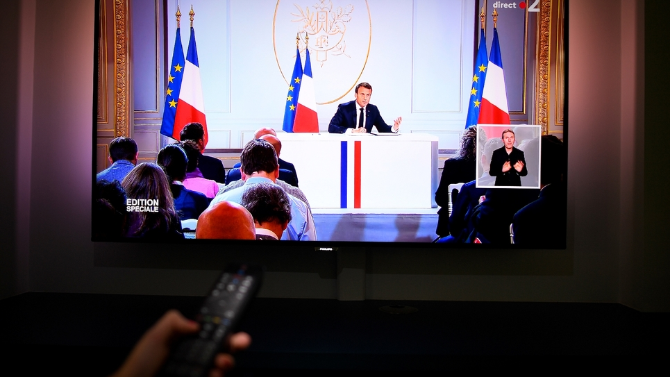 Emmanuel Macron sur un écran de télévision retransmettant sa conférence de presse, le 25 avril 2019 depuis l'Elysée