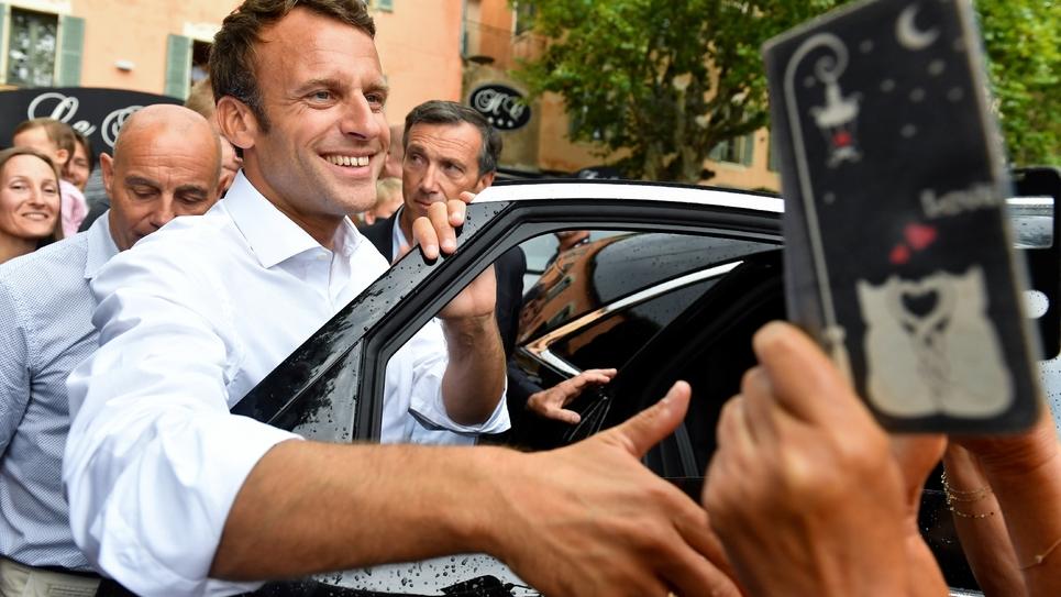 Le président Emmanuel Macron salue la foule après s'être entretenu avec le maire de la commune de Bormes-les-Mimosas (Var), le 27 juillet 2019