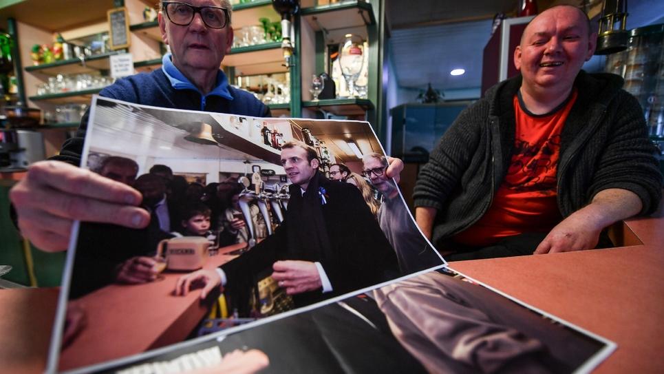 Les propriétaires d'un bar de Bully-les-Mines, avec les photos d'Emmanuel Macron en visite dans la ville en 2017 et 2018, le 2 avril 2019
