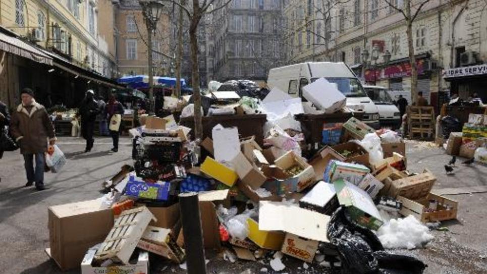 Une personne marche, le 12 mars 2010 sur une place de Marseille, où des ordures se sont accumulées du fait d'une grève d'éboueurs du secteur privé.