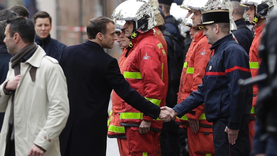 """Le président Macron salue les pompiers et gendarmes lors de sa visite dans les rues de Paris, le 2 décembre 2018 au lendemain des manifestations des """"gilets jaunes"""""""