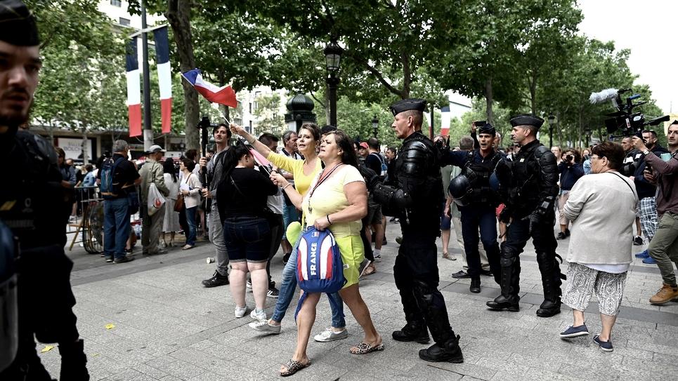"""Une femme """"gilet jaune"""" est entourée par les forces de l'ordre à Paris le 14 juillet 2019"""