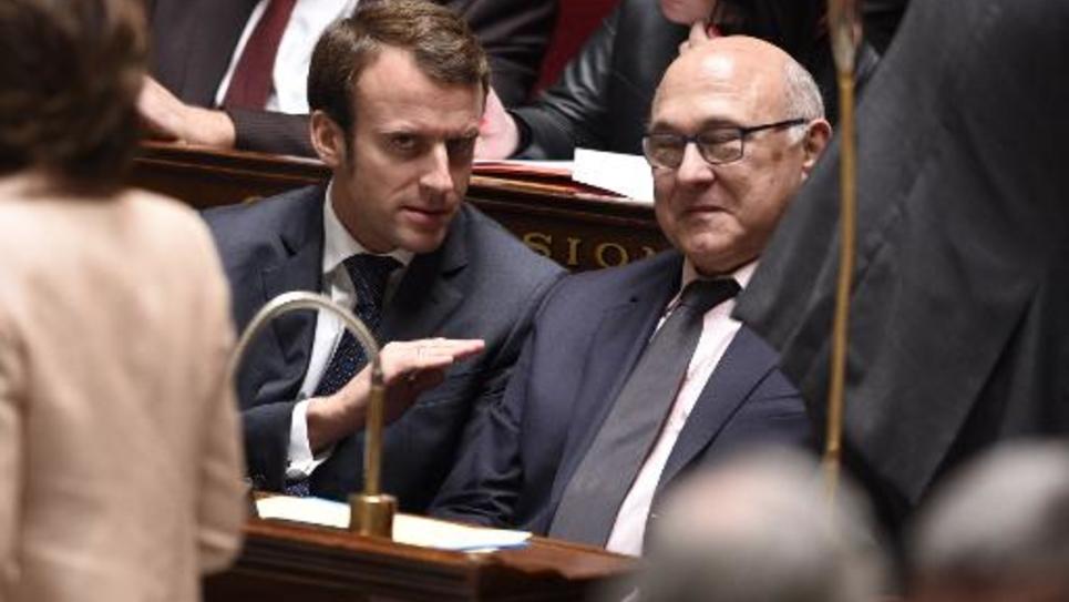 Le ministre de l'Economie Emmanuel Macron et le ministre des Finances Michel Sapin à l'Assemblée nationale le 15 octobre 2014 à Paris