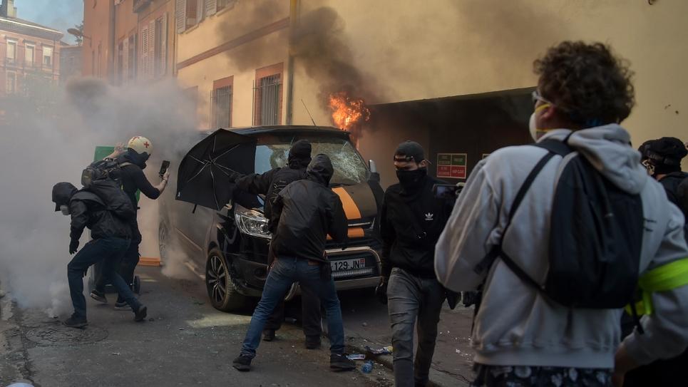 """Des """"gilets jaunes"""" affrontent la police près d'un véhicule incendié à Toulouse le 13 avril 2019, pour l'""""acte 22"""" du mouvement."""