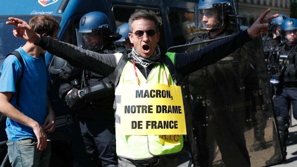 """Un militant porte une pancarte avec l'inscription """"Macron, notre drame français"""" en référence à l'incendie qui a dévasté Notre-Dame de Paris, le 20 avril 2019"""