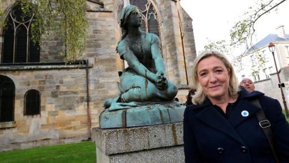 Marine Le Pen pose devant une statue de Jeanne d'Arc à Châlons-en-Champagne le 11 novembre 2014