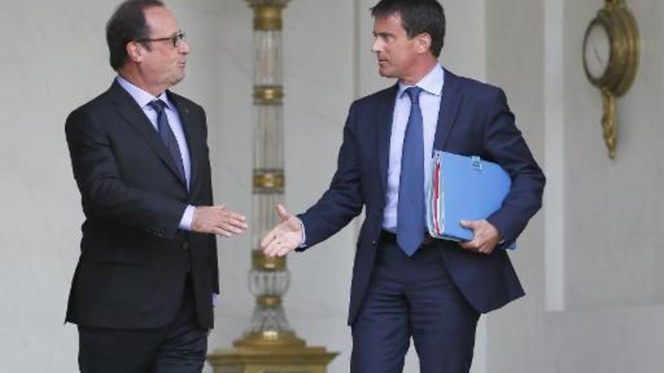 François Hollande et Manuel Valls se serrent la main à la sortie du conseil des ministres le 20 août 2014 sur le perron de l'Elysée à Paris