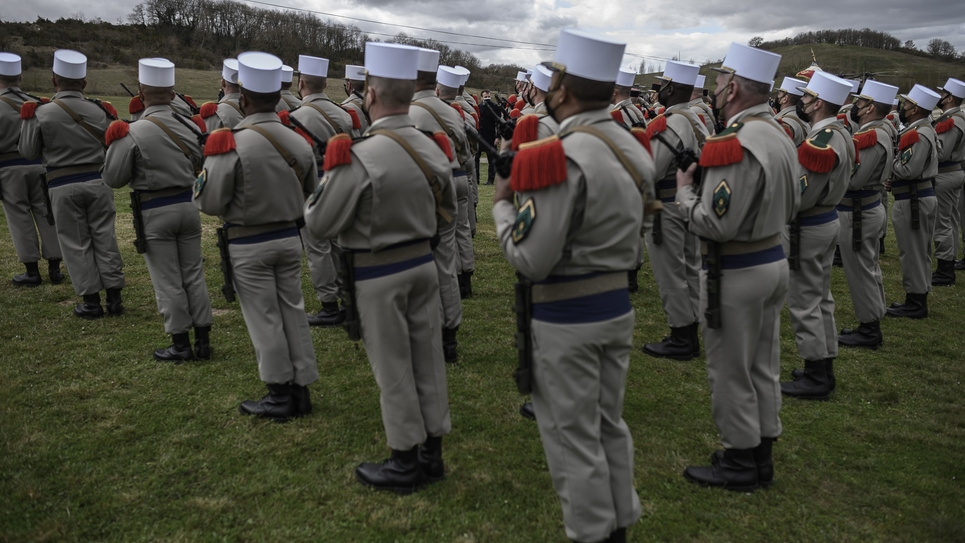 French President Emmanuel Macron reviews soldiers during a military honours ceremony at the Ferme du Cuin