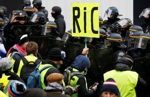 """Une pancarte réclamant l'instauration d'un référendum d'initiative citoyenne (RIC) est brandie lors d'une manifestation de """"gilets jaunes"""" à Paris, le 15 décembre 2018"""