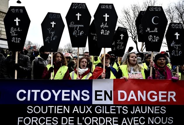 """Des """"gilets jaunes"""" manifestent, samedi 19 janvier 2019 à Paris, avec des pancartes en forme de cercueil évoquant les personnes tuées depuis le début du mouvement en novembre"""