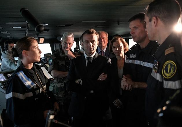 Emmanuel Macron dans la passerelle du porte-avions Charles de Gaulle en compagnie de la ministre de la Défense Florence Parly, du chef des armées le général Francois Lecointre et l'équipe de commandement du vaisseau, en Méditerrannée le 14 novembre 2018