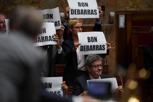 """Des membres de La France insoumise (LFI) brandissent des pancartes disant """"Bon débarras"""" en direction de Manuel Valls, le 2 octobre 2018 à l'Assemblée nationale"""