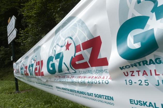 Une bannière pour le contre-sommet du G7 est installée sur un rond-point le 13 août 2019 à Louhossoa, à 30 km de Biarritz