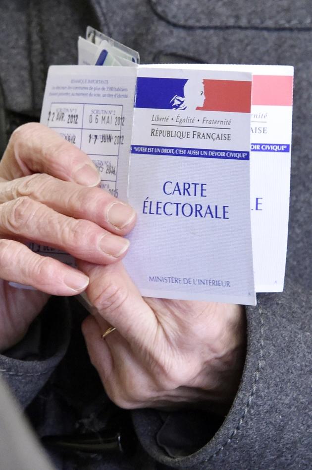 Une femme montre sa carte d'électrice au premier tour de la primaire élargie du PS à Nantes le 22 janvier 2017