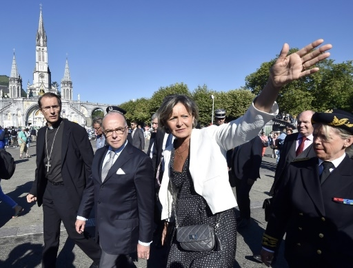 Le ministre de l'Intérieur Bernard Cazeneuve (c) entouré de l'évêque de Tarbes et de Lourdes Nicolas Brouwet (g), et de la maire de Lourdes Josette Bourdou (d), lors de sa visite à Lourdes, le 13 août 2016