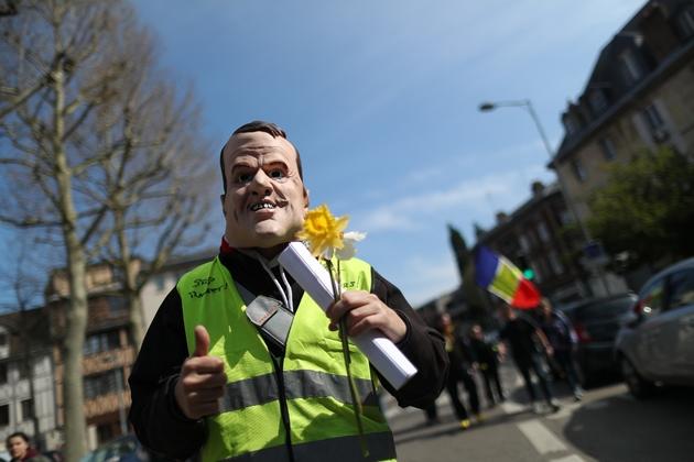 """Un """"gilet jaune"""" avec le masque de Macron défile à Rouen, le 6 avril 2019"""