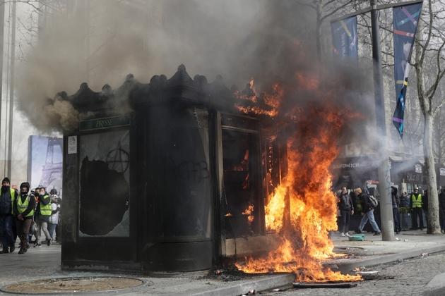 """Kioske à journaux en flammes sur l'avenue des Champs-Elysées lors de la manifestation des """"gilets jaunes"""" le 16 mars à Paris"""