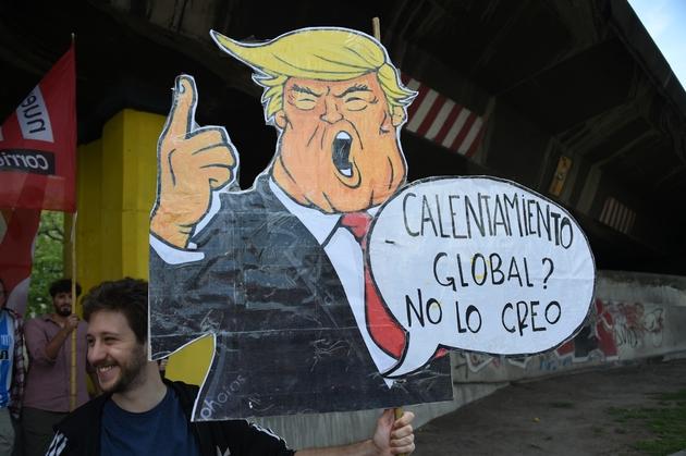 """Un homme porte une caricature de Donald Trump disant """"Réchauffement global? Je n'y crois pas"""", le 30 novembre 2018 à Buenos Aires. Le climatoscepticisme du président américain est un modèle pour les certaines Européens"""