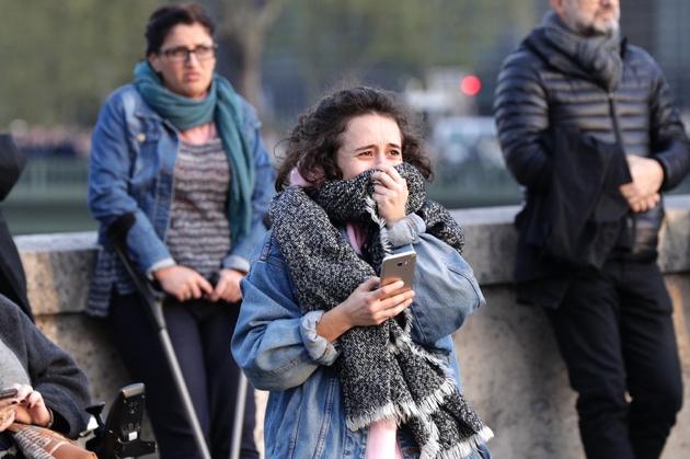 Une jeune femme en larmes devant Notre Dame en flammes, à Paris le 15 avril 2019