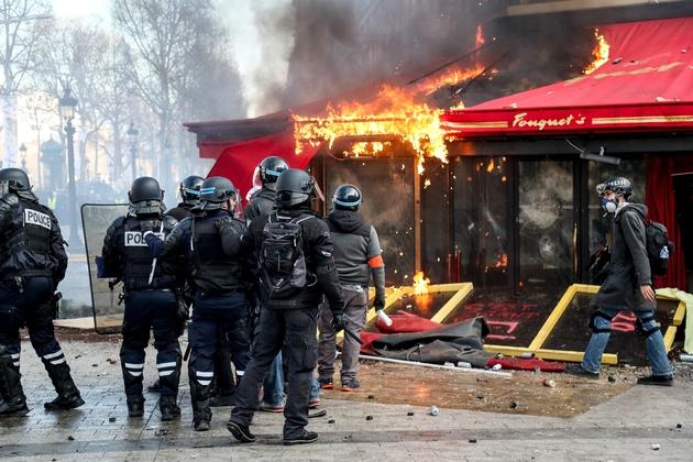 Les forces de police devant Le Fouquet's en feu, sur les Champs Elysées, à Paris, le 16 mars 2019