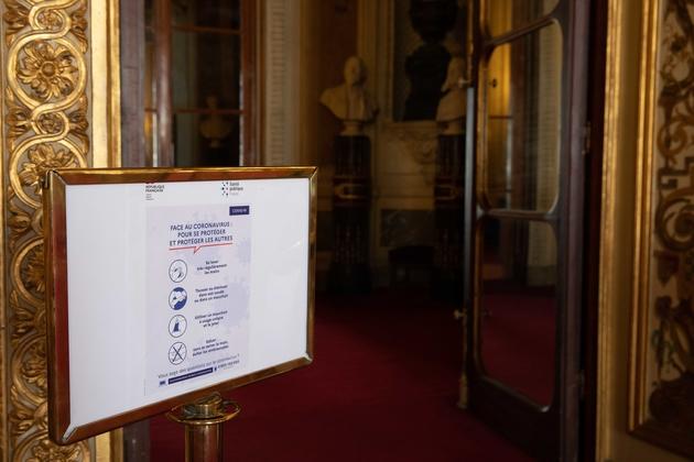 Une pancarte rappelle les gestes 'barrière' en salle des conférence du Sénat