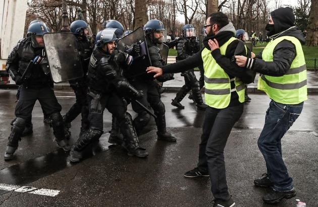 """Des """"gilets jaunes"""" face à des gendarmes mobiles lors de heurts en marge de la manifestation, le 22 décembre 2018 à Paris"""