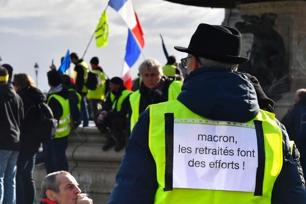"""Une affichette """"Macron, les retraités font des efforts"""" sur le dos d'un manifestation """"gilet jaune"""", le 19 janvier 2019 à Bordeaux"""