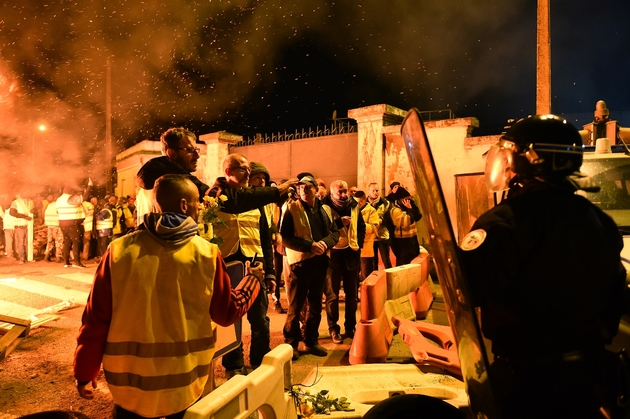"""Des """"gilets jaunes"""" font face aux forces de police devant un dépôt de carburant, le 29 novembre 2018 au Mans"""