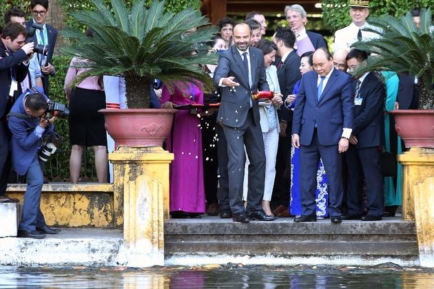 Le Premier ministre français Edouard Philippe (g), aux côtés de son homologue vietnamien Nguyen Xuan Phuc, nourrit des poissons au palais présidentiel, le 2 novembre 2018 à Hanoï