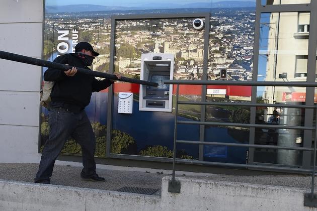 """Un manifestant casse un distributeur de billets en marge de la manifestation des """"gilets jaunes"""", le 30 mars 2019 à Avignon"""