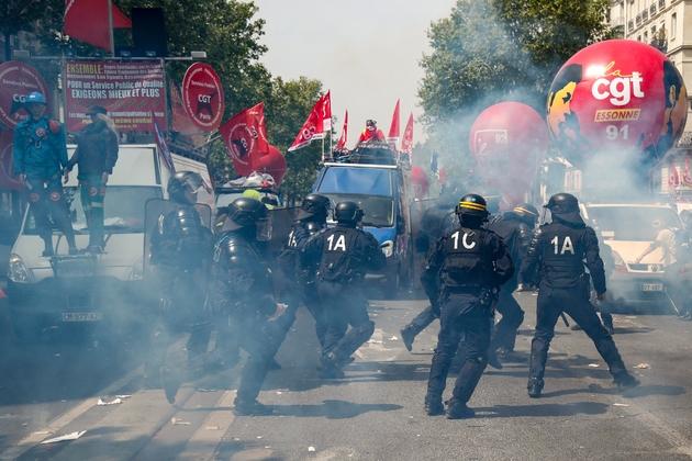 Des policiers passent en courant devant des véhciules de la CGT avant le départ des défilés du 1er mai 2019 à Paris