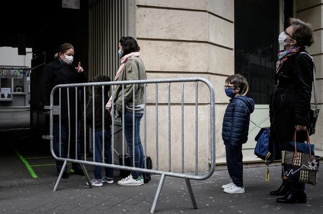 Des parents attendent avec leurs enfants devant l'entrée de l'école, le 12 mai 2020 à Paris