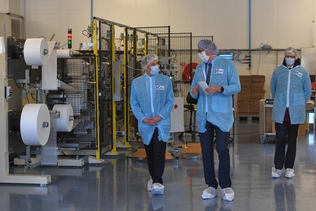 Le président Macron (g) visite la PME Kolmi-Hopen qui fabrique des masques, le 31 mars 2020 à Saint-Barthélémy-d'Anjou, près d'Angers