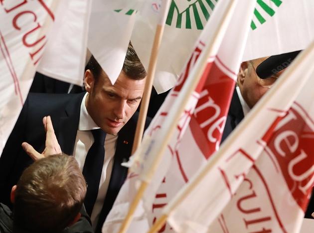 Le président Emmanuel Macron (D) discute avec des agriculteurs du syndicat FNSEA le 22 février 2020 à son arrivée au salon de l'agriculture à Paris