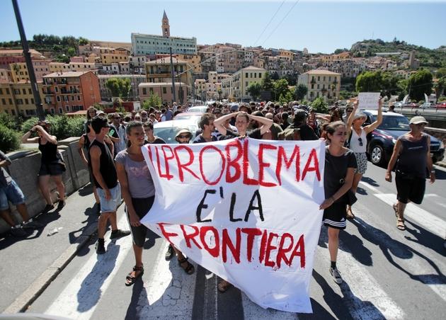 """Des militants du mouvement """"No Borders"""" (Pas de frontières) manifestent avec une banderole disant """"les frontières sont le problème"""" le 7 août 2016 à Vintimille, à la frontière franco-italienne"""