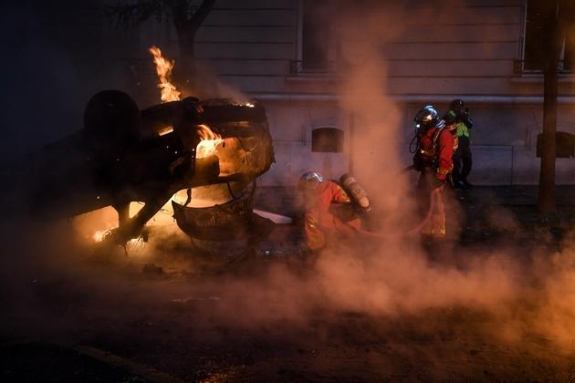 """Des pompiers luttent pour éteindre une voiture incendiée près des Champs-Elysées, dans le cadre de la manifestation des """"gilets jaunes"""", le 1er décembre 2018"""