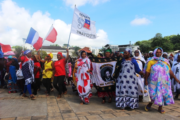 """Dans le cortège, en garde partie composé de mahoraises portant le salouva, flottaient de nombreux drapeaux français, européens, ou siglés """"département de Mayotte"""""""