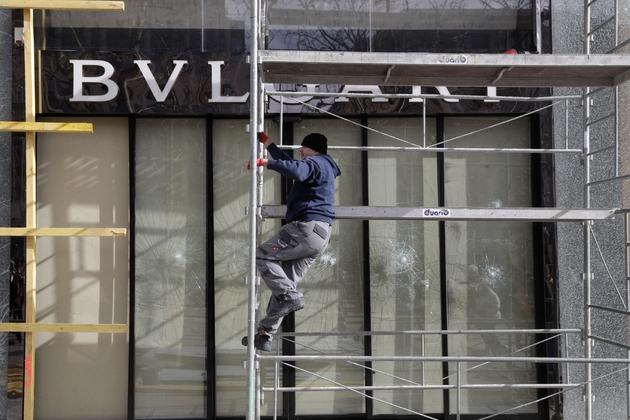 """Installation d'un panneau de bois devant la vitrine brisée d'une boutique sur les Champs-Elysées au lendemain de la manifestation des """"gilets jaunes"""", le 17 mars 2019 à Paris"""