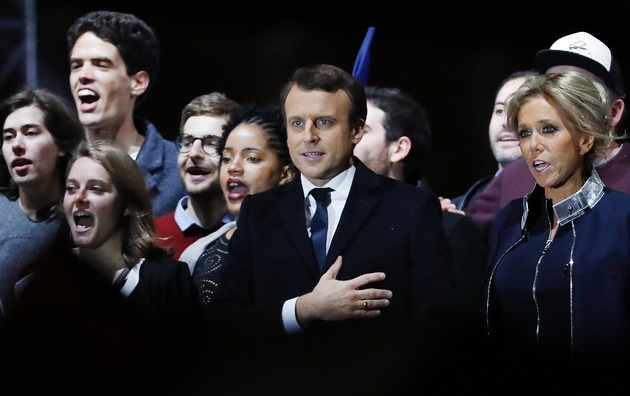Emmanuel Macron rejoint sur l'estrade par son épouse Brigitte, puis d'autres membres de sa famille, avant d'entonner une Marseillaise à leurs côtés, dans la cour du Louvre, le 7 mai 2017 à Paris