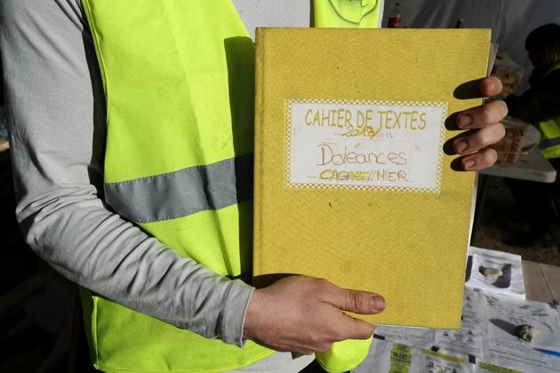 """Un """"gilet jaune"""" montre le cahier de doléances qu'il présente sur un rond-point à Cagnes-sur-mer, le 20 décembre 2018"""