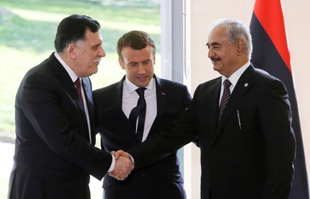 le Premier ministre libyen Fayez al-Sarraj (g) et le maréchal Khalifa Haftar (d), l'homme fort de l'est libyen, se serrent la main en présence du président Emmanuel Maron, le 25 juillet 2017 à la Celle-Saint-Cloud, près de Paris