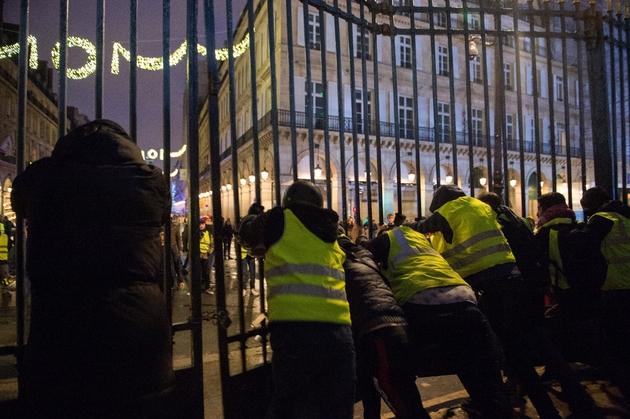 """Des manifestants dont des """"gilets jaunes"""" forcent des grilles au jardin des Tuileries à Paris, le 1er decembre  2018"""